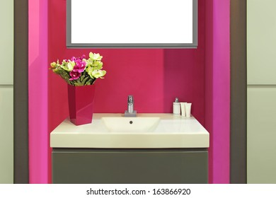 Fragment of a luxury purple bathroom and flowers in a vase on the sink