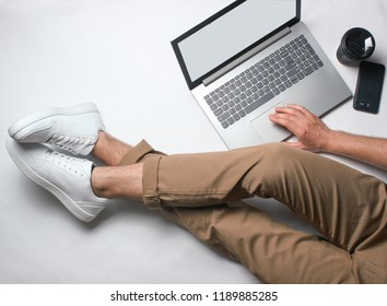 Fragment of male legs in beige pants and white sneakers sitting on white. Man using modern laptop. Online worker, freelancing, work at home, man working. top view on white background