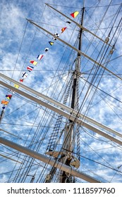 fragment of a mast of a marine schooner and signal flags against a blue sky
