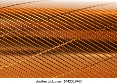 A fragment of a metal object with diagonal notches and a golden hue. Background and pattern. Daylight.