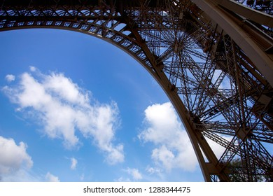 Fragment of a metal structure of the Eiffel Tower against a blue sky and clouds