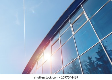 Fragment of modern glass building of airport, office or sports facility, blue sky background.