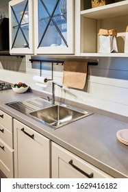 Fragment of a modern kitchen with wooden facades and a double metal sink
