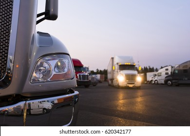 Fragment of the modern parts of the truck on a night truck stop in the foreground to the background of semi trucks at the parking places and a moving semi truck with its headlights on.