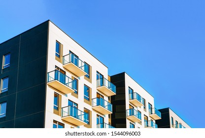Fragment of Modern residential apartment with flat buildings exterior. Detail of New luxury house and home complex. Part of City Real estate property and condo architecture. Copy space. Blue sky