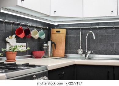 A fragment of the modern style kitchen with rail system and kitchen utensils and houseplant