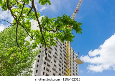 Fragment of the multi story residential house from precast concrete panels during construction and raised building panel by a crane across branches of trees