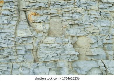 Fragment of natural limestone cliff in Kesselaid (also Kessulaid) islet nordic coast. Tiny island in Suur Strait, Baltic Sea Layers of cracked rocks. Texture of  hard sedimentary rock. Estonian coast.