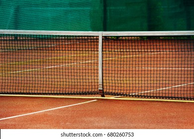 A fragment of a net on a  tennis clay court