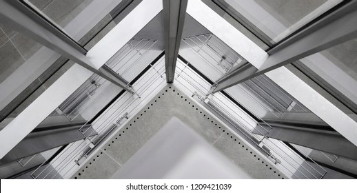 Fragment of office building interior featuring corner of structural glazing. Hi-tech architecture made of steel / aluminum and glass. Material background on the subject of construction industry.