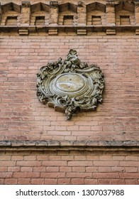 A fragment of the old brick wall with a floral Cartouche (cartouch), detail of facade. Oval design with a slightly convex surface, edged with ornamental scrollwork and plant ornament