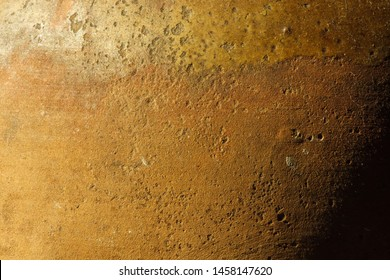 A fragment of an old clay pot. The surface of the ceramic product. Texture. Close-up. The small depth of field