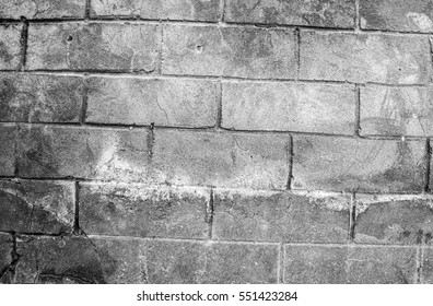 Fragment of old dirty brick wall with peeling plaster texture white grey, stone surface with cracks, useful as background toned