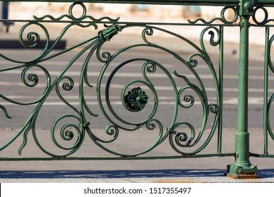 Fragment of an old elegant forged street fence. vintage green metal city fencing