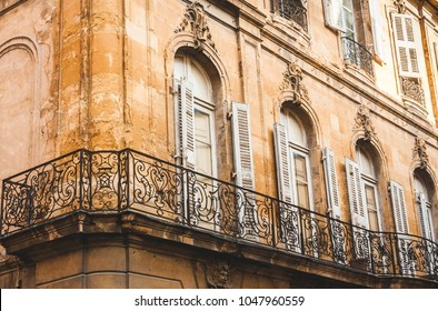 Fragment of old house in decay with forged balcony railings in Aix-en-Provence, France