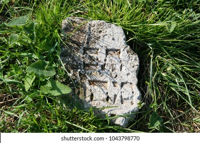 A fragment of old matzevah (Jewish stone tombstone) with letters in Hebrew in the thick green grass in the ukrainian village of Zhvanets near Kamianets-Podilsky, Western Ukraine. Forgotten cemetery.