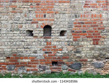 Fragment of the old red  brick fortress wall with loopholes for shooting from muskets and crossbows. Historical background