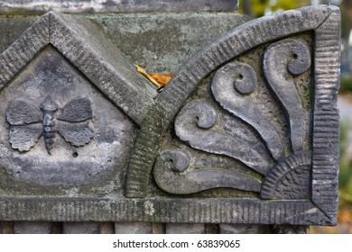 Fragment of an old sculptured gravestone in autumn