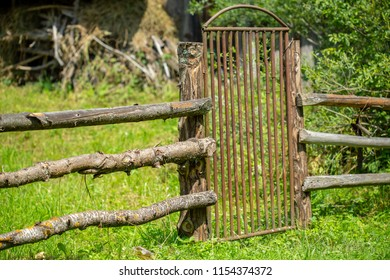 Fragment of an old wooden fence with an iron gate.