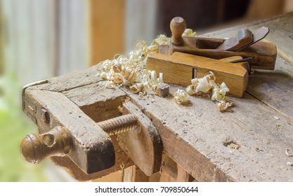 Fragment of old woodworking workbench with planing stop and shoulder vise with wooden screw, two wooden hand planes lying on workbench among a shavings