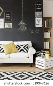 Fragment of optimistic living room with white sofa and motivational phrases on the wall