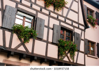 Fragment of an orange facade of an old timber house with windows with shutters and blooming flowers in Colmar, France