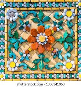 Fragment des Ziermosaikmusters mit vielen bunten Blumenelementen. Zierfliesen-Struktur aus dem Wat Pho Tempel