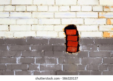 A fragment of a painted brick wall. The wall has a hole with carelessly stacked red bricks. Russia, Moscow Region, June 2015.