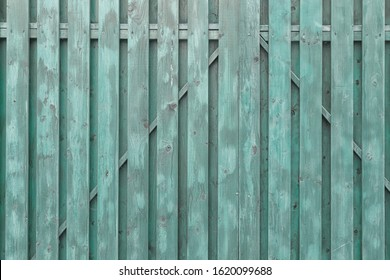 A fragment of a painted wooden gate. The structure of the boards and battens. Turquoise surround background.