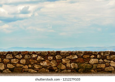 fragment or part of an ancient stone wall of fortress against the background of the sky
