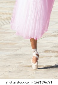 Fragment photo of ballerina legs in warm bright background. Body part. Ballerina performing in the street. Feet fragment. Artist. Lifestyle. Elegance and grace