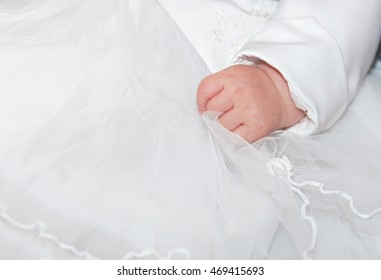 Fragment photo of little baby girl preparing for baptism ceremony, hand on a white dress, hand of baby on a baptism dress on christening day. Baby hand with ceremonial clothes. Baptism