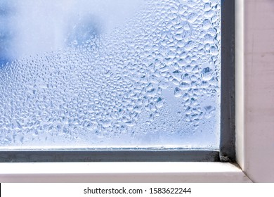 A fragment of a plastic window with condensation of water on the glass. Concept: defective plastic window with condensation, temperature difference, cooling, humidity in the room.