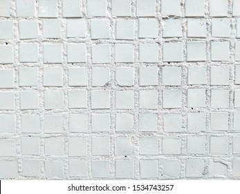 fragment of a real wall to which small pieces of square mosaic of the same size and color are glued.abstract background for your design.close-up.