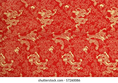 Fragment of red chinese silk with golden dragons and flowers
