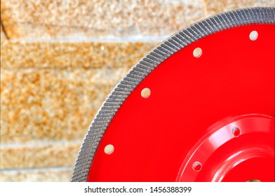 Fragment of a red diamond blade for cutting granite and stone against a background of a wall of golden sandstone.