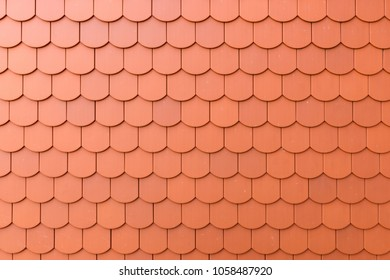 Fragment of a red roof of a private house made of shingles