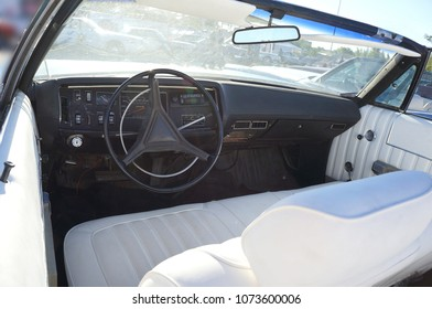 Fragment retro car dashboard.  White leather and black steering wheel.