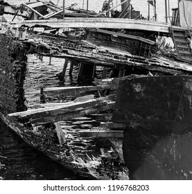 Fragment of rotting, abandoned ship on the shore, a symbol of decadence and degradation, a monochrome image