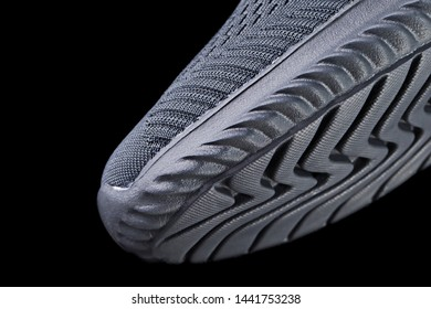 Fragment of a rubber black sole sneaker. Bottom of sports shoes