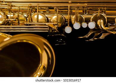 Fragment of saxophone on a black background