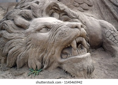 Fragment of sculpture from sand on the theme of mythology. Tearing lion, fangs of muzzle. Statues of sand close-up
