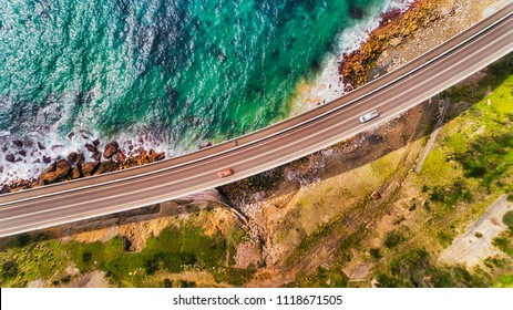 Fragment of the Sea Cliff Bridge on Grand Pacific Drive scenic motorway in Australian NSW state along pacific coast in aerial top down view.