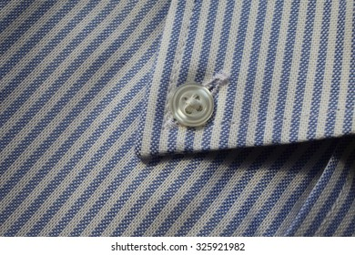 Fragment of shirt close up. Fabric in blue and white stripes with a button.