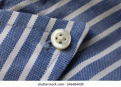 Fragment of shirt. Fabric in blue and white stripes with a button.