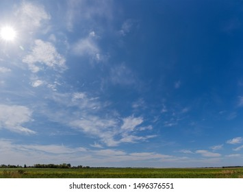 Fragment of the sky with cirrus and cumulus clouds and sun over field