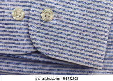 Fragment of sleeve cotton shirt. Pure cotton fabric in blue and white stripes with buttons.