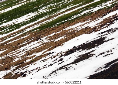 A fragment of a slope to a river. The slope includes open brown ground, green grass and partially covered with white snow. Russia, city of Kaluga, February 2016.