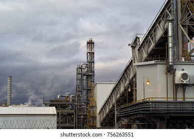 a fragment of some large refinery with a variety of technical designs, a distillation column, a covered conveyor structure and burning lanterns in the evening