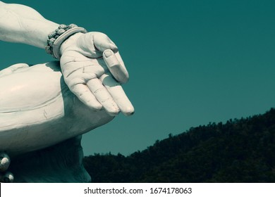 Fragment of a statue of Shiva meditating in lotus position. Shiva's hand against the sky. Toned photo.